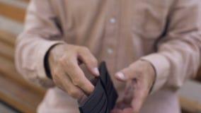 Homem envelhecido que mostra a carteira vazia, crise financeira, economias da aposentadoria, necessidade video estoque