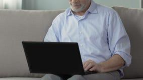 Homem envelhecido que senta-se no sofá, usando o portátil, trabalhando da casa, projetando o projeto vídeos de arquivo