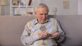 Homem envelhecido triste que senta-se no sofá e que conta moedas na palma, insegurança social filme