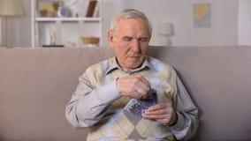 Homem envelhecido virado que senta-se no sofá, guardando cédulas dos euro, insegurança social filme