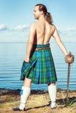 Homem escocês com a espada perto do mar Foto de Stock Royalty Free