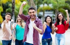 Homem espanhol Cheering do moderno com grupo feliz de amigos imagem de stock