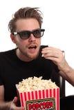 Homem espantado em 3D-glasses com uma cubeta da pipoca Imagem de Stock Royalty Free