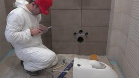 Homem especializado do encanador que trabalha na montagem da mão da bacia de toalete no banheiro moderno novo vídeos de arquivo