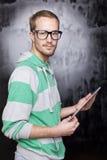 Homem esperto bem parecido do lerdo com computador da tabuleta Imagens de Stock Royalty Free