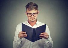 Homem esperto no livro de leitura dos vidros fotos de stock royalty free