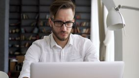 Homem esperto que trabalha pelo computador no espaço de trabalho video estoque