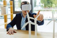 Homem esperto sério que senta-se na frente do modelo do moinho de vento Imagens de Stock Royalty Free