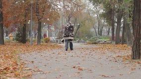 Homem estranho que vagueia no parque da cidade coberto com a cobertura, pessoa mentalmente doente vídeos de arquivo