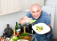 Homem europeu com uma faca e uma placa da salada em sua mão no th Imagens de Stock