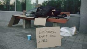 Homem europeu desabrigado e desempregado com sono do sinal do cartão no banco na rua da cidade devido à crise dos imigrantes dent video estoque