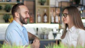 Homem europeu e mulher que riem e que têm o assento de encontro informal na barra filme