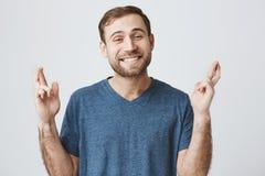 Homem europeu farpado no t-shirt azul que fecha seus olhos que cruzam os dedos com esperança ao antecipar a notícia importante Fotos de Stock Royalty Free