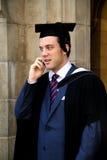 Homem europeu novo em um vestido da graduação. Fotos de Stock