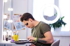 Homem exato interessado com mão tattooed observando a composição nova fotografia de stock