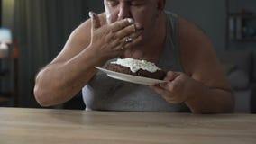 Homem excesso de peso adulto que devora o bolo e que lambe seus dedos, diabetes, comida lixo filme
