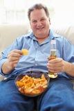 Homem excesso de peso em casa que come Chips And Drinking Beer fotos de stock