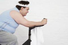 Homem excesso de peso na bicicleta de exercício Foto de Stock Royalty Free