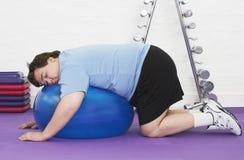 Homem excesso de peso que dorme na bola do exercício imagens de stock