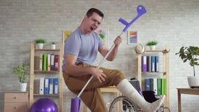 Homem expressivo com uma dança do pé enfaixado com as muletas no centro de reabilitação mo lento filme