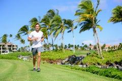 Homem exterior do exercício que corre na grama no parque da cidade Fotos de Stock