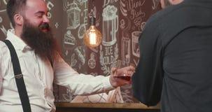 Homem farpado à moda que bebe de um vidro do uísque em um contador da barra vídeos de arquivo