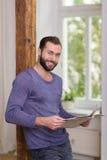 Homem farpado amigável que relaxa com um jornal Fotografia de Stock