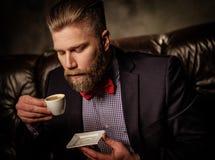 Homem farpado antiquado que senta-se no sofá de couro confortável com a xícara de café isolada no cinza Imagem de Stock Royalty Free