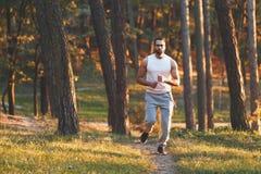 Homem farpado atlético que movimenta-se na floresta imagens de stock royalty free