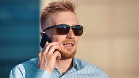 Homem farpado bem sucedido seguro da cara do close-up nos óculos de sol que discute o negócio usando o smartphone filme