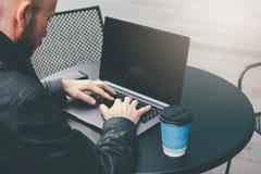 Homem farpado calvo bem sucedido adulto atrativo de pensamento no revestimento preto com o portátil no café da rua na cidade foto de stock