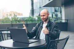 Homem farpado calvo bem sucedido adulto atrativo de sorriso no revestimento preto com o portátil no café da rua na cidade fotografia de stock