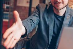 Homem farpado calvo bem sucedido adulto atrativo de sorriso no terno com o portátil que dá o aperto de mão, mão da ajuda, cumprim fotografia de stock