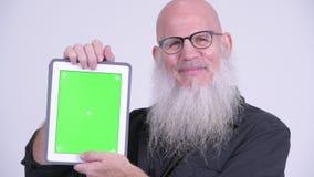Homem farpado calvo maduro feliz que mostra a tabuleta digital vídeos de arquivo