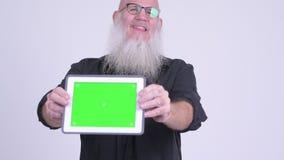Homem farpado calvo maduro que mostra a tabuleta digital video estoque