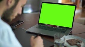 Homem farpado caucasiano da habilidade que usa a tabuleta gráfica e o portátil no escritório Trabalhador masculino que olha o des video estoque
