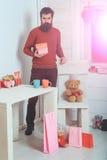 Homem farpado com as caixas de presente na tabela com copos Fotos de Stock