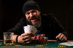 Homem farpado com o charuto e o vidro que sentam-se na tabela do pôquer e que gritam no preto Imagem de Stock