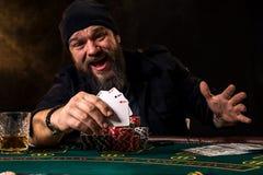 Homem farpado com o charuto e o vidro que sentam-se na tabela do pôquer e que gritam no preto Imagem de Stock Royalty Free