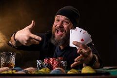 Homem farpado com o charuto e o vidro que sentam-se na tabela do pôquer e que gritam no preto Fotos de Stock Royalty Free