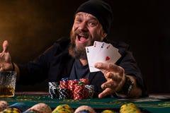 Homem farpado com o charuto e o vidro que sentam-se na tabela do pôquer e gritar isolado no preto Foto de Stock