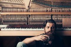 Homem farpado com o piano de madeira próximo de vidro fotos de stock royalty free