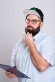 Homem farpado com prancheta e boné de beisebol Fotos de Stock