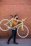 Homem farpado com uma bicicleta do fixie Homem farpado novo seguro que leva sua bicicleta no ombro e que olha a câmera ao andar fotos de stock