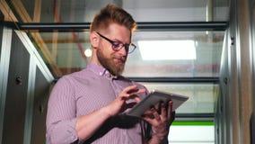 Homem farpado com uma tabuleta em uma sala do servidor vídeos de arquivo