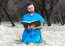 Homem farpado considerável concentrado no assento azul do quimono, guardando o grande livro aberto e a leitura fotos de stock