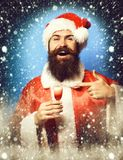 Homem farpado considerável de Papai Noel com a barba longa na cara de sorriso que guarda o vidro do tiro alcoólico no Natal verme imagens de stock royalty free