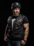 Homem farpado considerável do motociclista do retrato no casaco de cabedal e no capacete Imagens de Stock