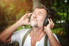 Homem farpado considerável em seu 50s com fones de ouvido Imagem de Stock Royalty Free