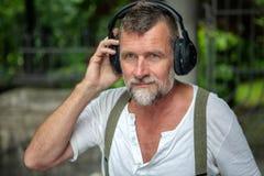 Homem farpado considerável em seu 50s com fones de ouvido Imagens de Stock